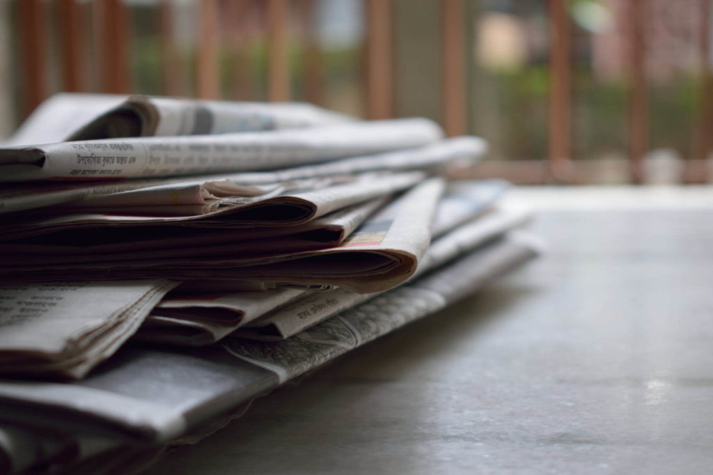 A pile of newspapers on a table