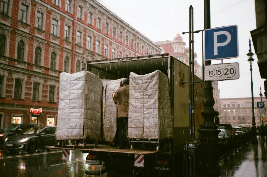 a truck full of items parked in a busy street in the rain